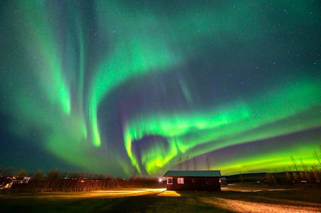 Aurora dançando acima da cabana em uma pequena cidade no interior da islândia
