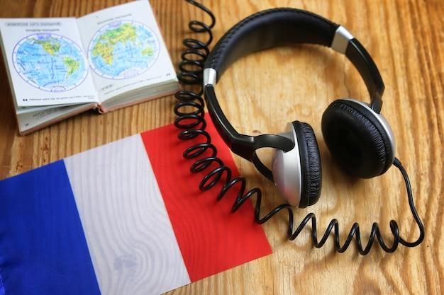 Auscultadores do curso de línguas e bandeira na mesa de madeira
