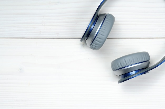 Auscultadores modernos em azul e prateado para ouvir música em madeira branca