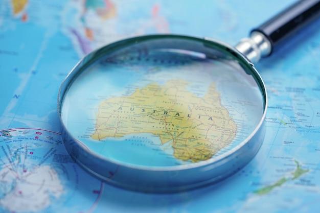 Austrália: lupa com mapa de luva do mundo.