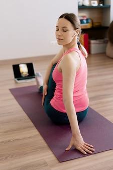 Autêntica mulher praticando ioga em casa