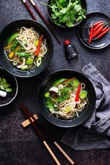 Autêntica sopa asiática de macarrão em tigela preta