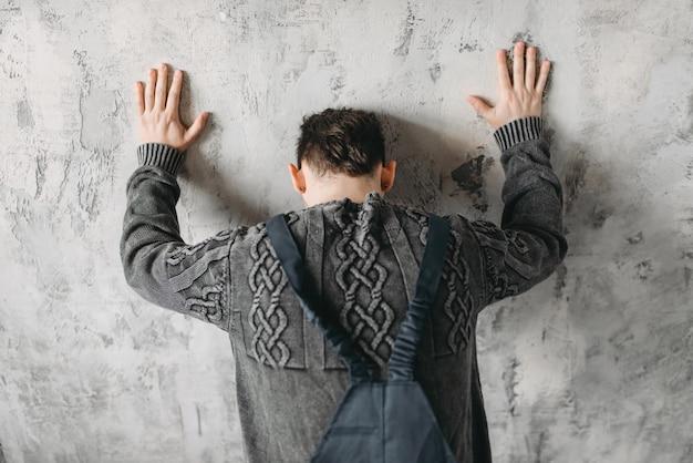 Autista fica de frente para a síndrome da parede, interior da sala do grunge.