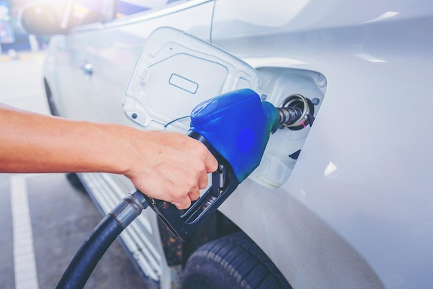 Auto carro branco de reabastecimento com gasolina no posto de gasolina.