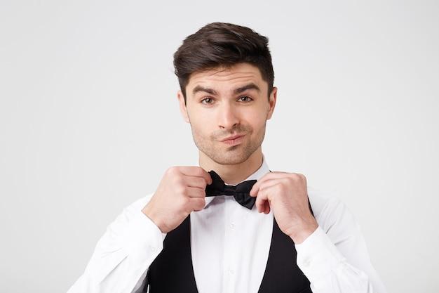 Auto-confiante usando um terno elegante que endireita a gravata borboleta preta