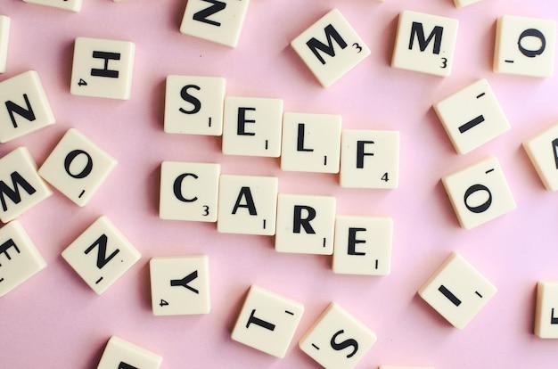 Auto-cuidado - texto em cubos de madeira em um fundo rosa