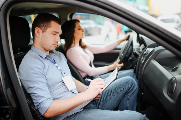 Auto instrutor masculino faz exame em jovem. homem ocupado, sério e concentrado escrevendo resultados de testes em papel. motorista do sexo feminino confiante ansioso na estrada. passando no exame de condução