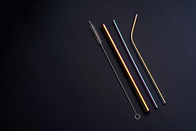 Auto kit de canudos metálicos reutilizáveis para bebidas de vários diâmetros, cores e formatos com ferramenta de limpeza. em fundo preto.
