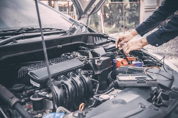 Auto mecânico usando a ferramenta de equipamento de medição para verificar a bateria do carro.