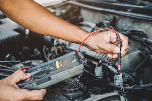 Auto mecânico usando a ferramenta de equipamento de medição, verificando o carro elétrico.