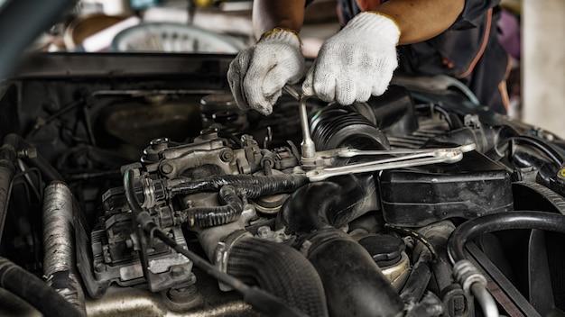 Auto mechanic preparing para o trabalho. mecânico com chave de aço inoxidável na mão.