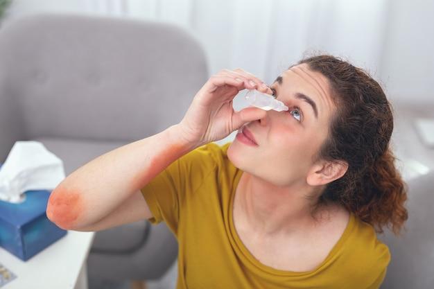 Auto-medicação. mulher jovem com aparência de sicl tentando fazer autotratamento no olho infectado sem a ajuda de ninguém