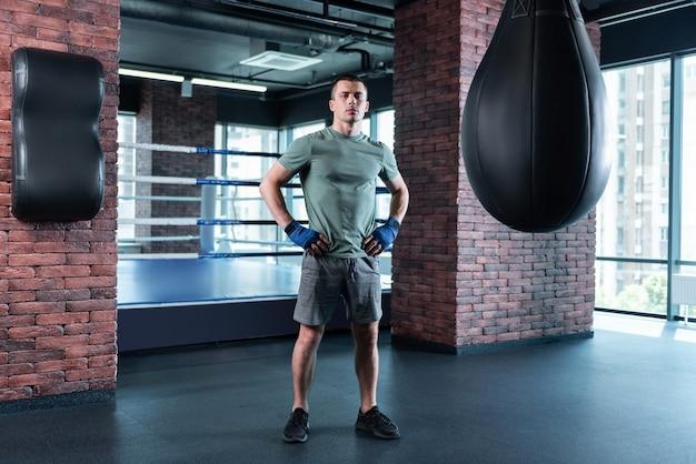 Auto-motivação. boxeador forte de cabelos escuros vestindo shorts cinza e camisa cáqui se motivando antes da competição