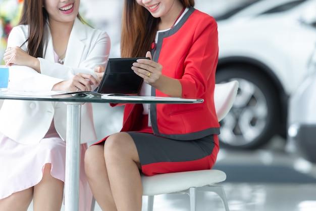 Auto negócio asiático, venda do carro, tecnologia e conceito dos povos - par feliz com carro.