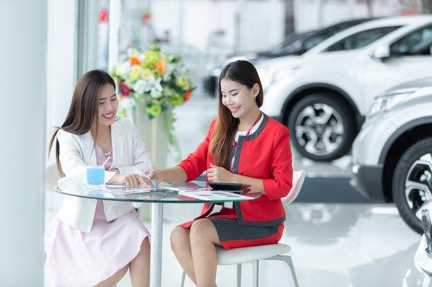 Auto negócio asiático, venda do carro, tecnologia e conceito dos povos - par feliz.