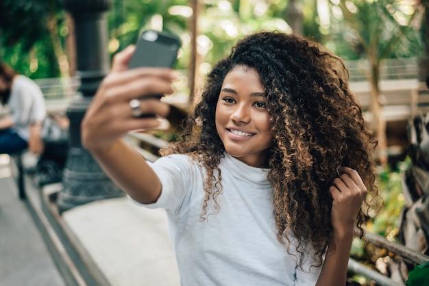 Auto-retrato da mulher nova bonita com penteado afro.
