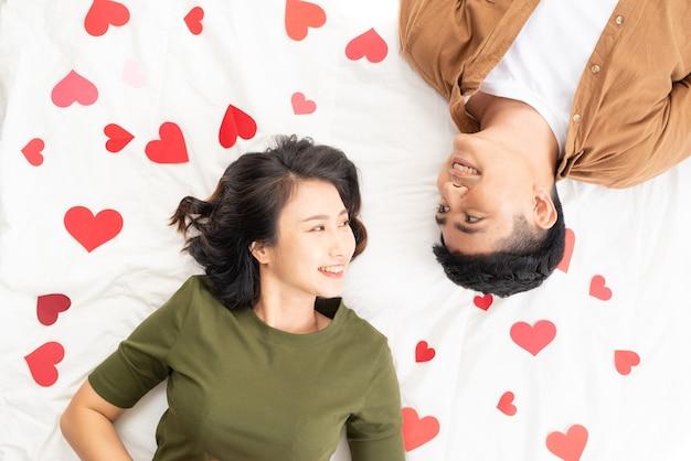 Auto-retrato de casal fofo e doce deitado no chão com pequenos corações vermelhos.