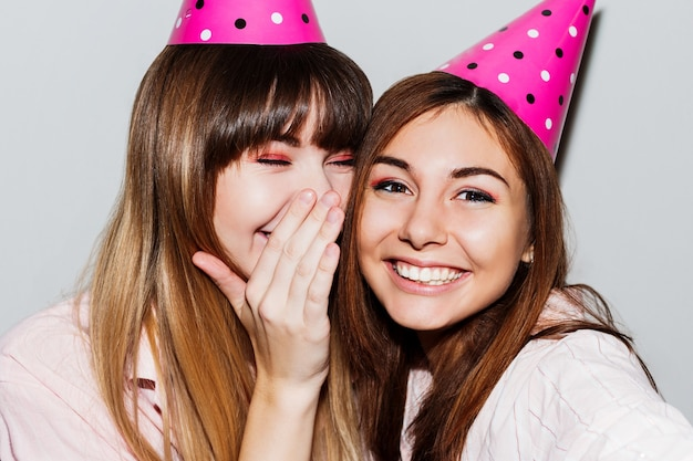 Auto-retrato de duas mulheres com chapéus de aniversário de papel rosa. amigos de pijama rosa. humor lúdico.