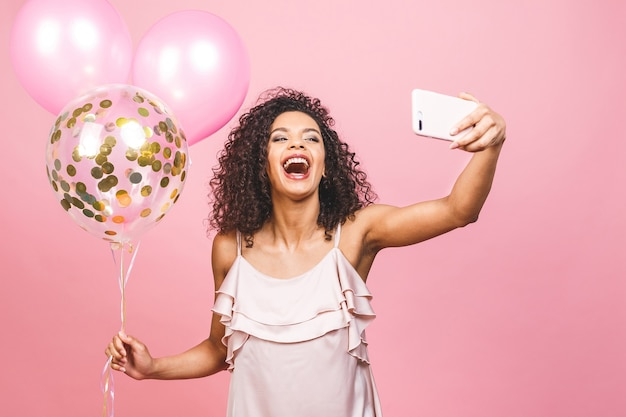 Auto-retrato de garota afro-americana positiva em vestido com balões na mão, tirando selfie na câmera frontal isolada no fundo rosa.