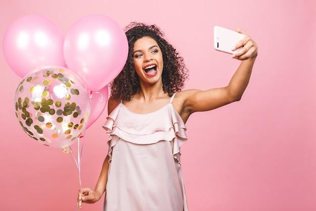 Auto-retrato de garota afro-americana positiva em vestido com balões na mão tirando selfie