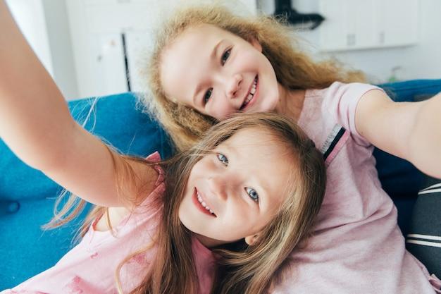 Auto-retrato de irmãs loucas e tolas, rindo, juntos fazendo selfie no celular em casa