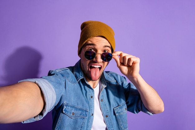 Auto-retrato de um homem tolo, casual engraçado, hilário, ridículo, tirando uma selfie mostrando a língua usando uma jaqueta jeans, boné marrom, chapéu isolado sobre fundo de cor roxa vívida