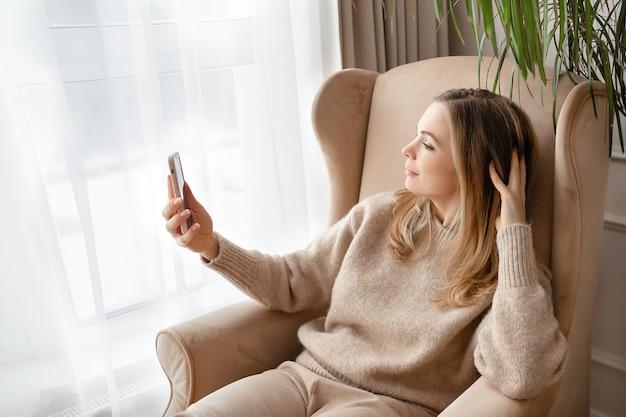 Auto-retrato de uma jovem loira bonita com uma camisola de malha bege. conceito de selfie e videochamada