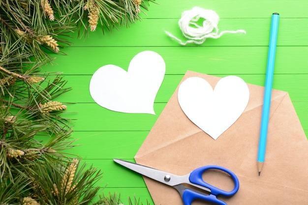 Autocolantes em forma de coração com envelope entre ramos de pinheiro sobre fundo verde de madeira