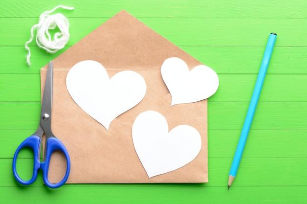 Autocolantes em forma de coração com um envelope sobre fundo verde de madeira