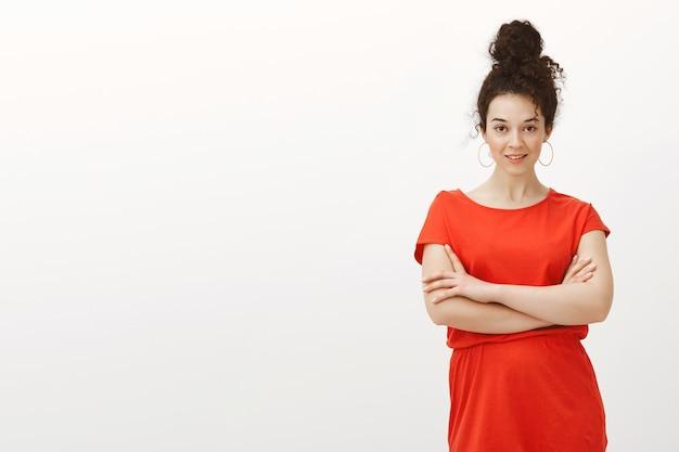 Autoconfiante e atrevida colega de trabalho caucasiana em um vestido da moda, de mãos cruzadas no peito