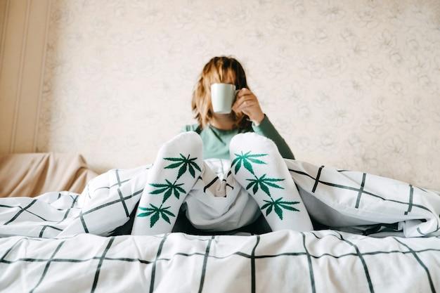 Autocuidado, calma, rotina de luto, dia de início. saúde mental, autocuidado, sem estresse, hábito saudável, conceito de uso de maconha para ansiedade. mulher em meias com folhas de maconha começa o dia na cama.