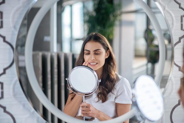 Autocuidados. uma mulher olhando para o pequeno espelho em seu banheiro