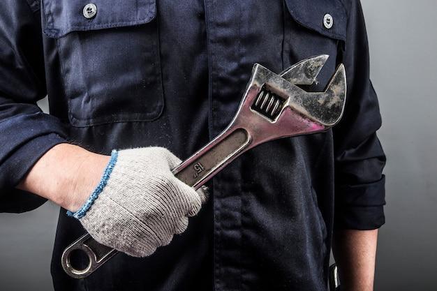 Automechanic em macacão segurando chave ou chave inglesa