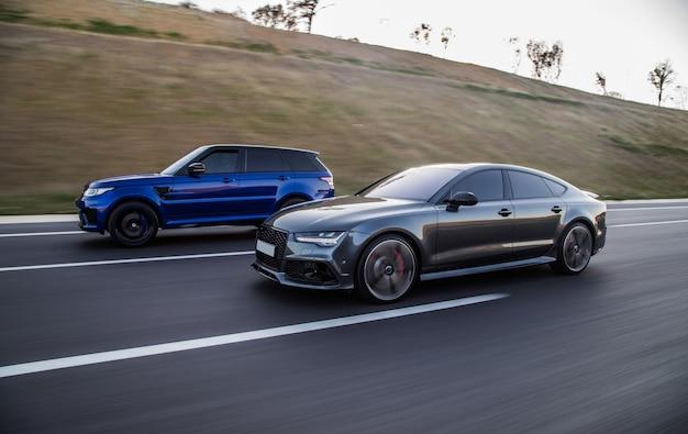 Automobilismo de um jipe azul e um carro esporte cinza sedan.
