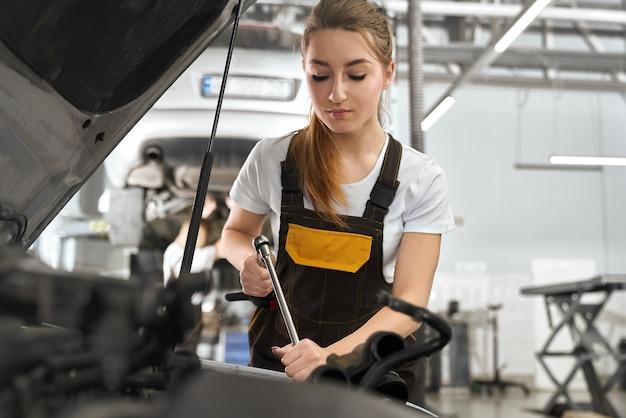 Automóvel de fixação mecânico feminino sob o capô.