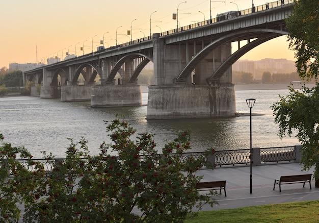Automóvel grande ponte em arco sobre o dique do rio ob com árvores