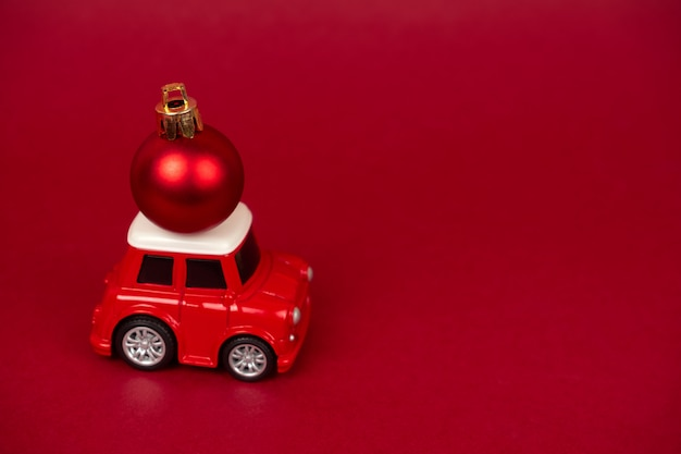 Automóvel vermelho pequeno bonito com bola vermelha de natal