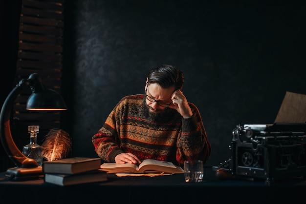 Autor barbudo de óculos lendo um livro
