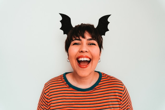 Autorretrato de uma sorridente mulher branca com uma faixa em forma de morcego