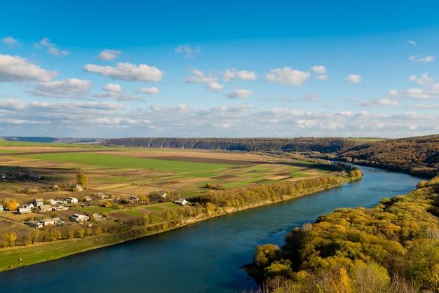 Autumn landscape - rio, céu com nuvens, campos.
