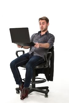 Auxiliar de obras com um laptop na mão enquanto está sentado em uma cadeira, fundo branco do estúdio