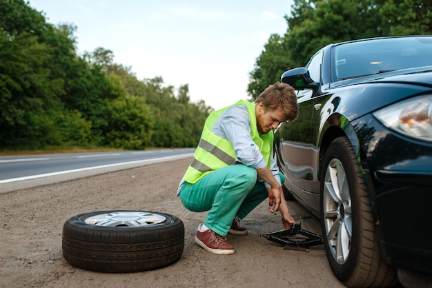 Avaria do carro, jovem reparando um pneu furado. automóvel quebrado ou problema com o veículo, problema com pneu furado na rodovia
