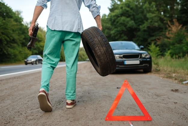 Avaria do carro, o homem coloca o pneu sobressalente.