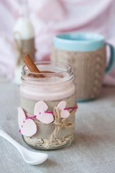 Aveia, aromatizada com iogurte, polvilhada com canela em uma jarra de vidro. em seguida é uma xícara de café e uma garrafa de leite. em seguida é um caderno de artesanato e um guardanapo rosa.