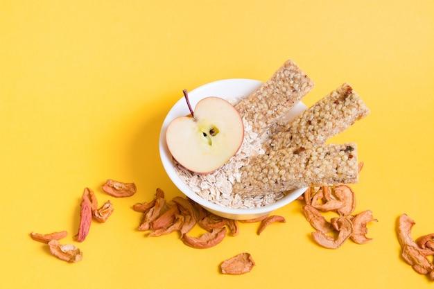 Aveia, barras de aveia e maçã em fundo amarelo, conceito de nutrição adequada