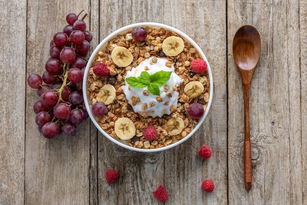 Aveia com framboesas, uvas e banana em um fundo de madeira. mingau de café da manhã com frutas.