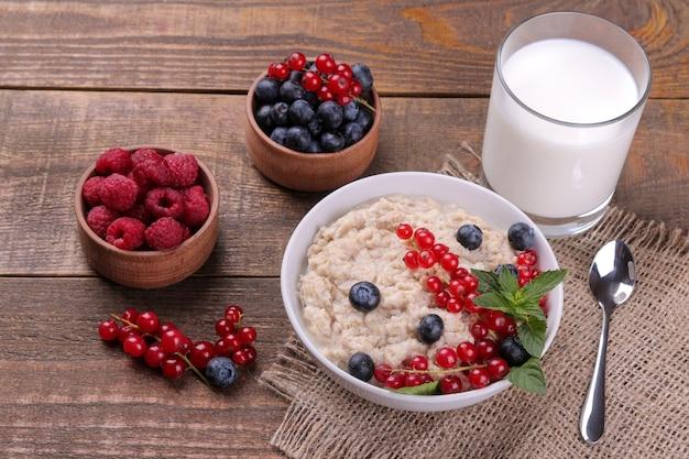 Aveia com frutas e leite em uma tigela sobre uma mesa de madeira marrom. café da manhã. comida saudável.