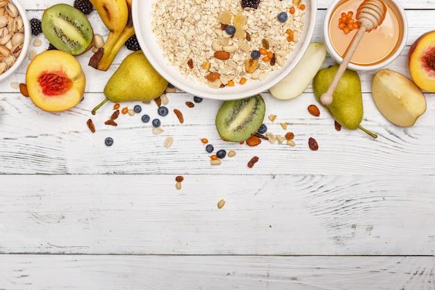 Aveia com frutas e mel em uma mesa de madeira branca