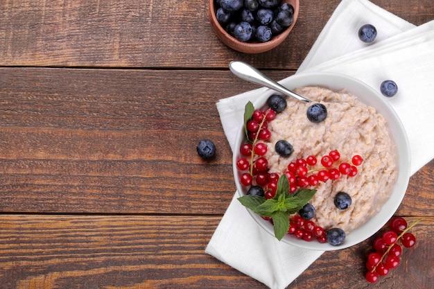 Aveia com frutas em uma tigela sobre uma mesa de madeira marrom. café da manhã. comida saudável. vista do topo