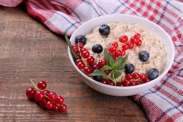 Aveia com frutas em uma tigela sobre uma mesa de madeira marrom. café da manhã. comida saudável.